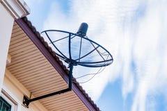 Una antena parabólica en el tejado imagen de archivo