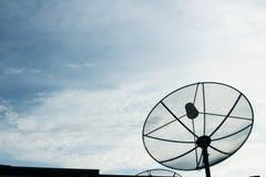 Una antena parabólica negra en el fondo crepuscular del cielo Fotos de archivo libres de regalías