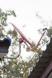 Una antena parabólica roja en el tejado Imagen de archivo libre de regalías