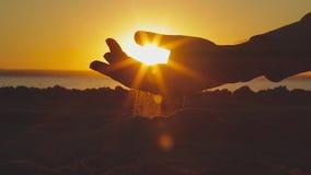Una arena pasa a través de las manos en un fondo de la puesta del sol almacen de video