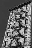 Una arenisca de color oscuro típica de New York City con la salida de incendios en fuera del edificio, en blanco y negro, NY, los fotografía de archivo
