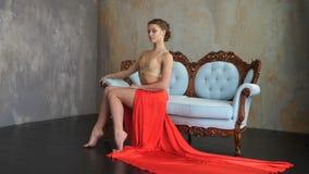 Una bailarina hermosa joven en una falda y un top largos rojos se sienta a un sofá retro de madera hermoso con un equipo azul almacen de video