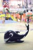Una ballena inflable graciosamente miente cerca de piscina Fotos de archivo