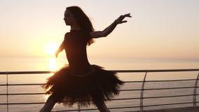 Una ballerina che pratica un ballo di balletto vicino al mare Preparando e facendo un salto Luce solare di Wondeful sul dietro le video d archivio