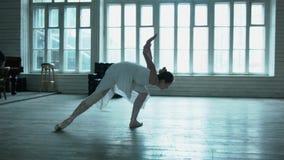 Una ballerina nel bianco balla in un corridoio con le grandi finestre Nei precedenti, un giovane sta giocando il piano La ragazza stock footage