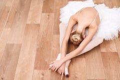 Una ballerina professionista sta sedendosi sul pavimento in una classe di ballo Fotografie Stock