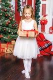 Una bambina apre un contenitore di regalo Nuovo anno di concetto, Christma allegro Fotografie Stock