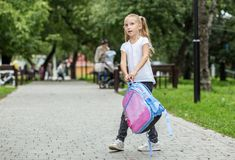 Una bambina cammina con uno zaino nel cortile della scuola Il concetto di scuola, studio, istruzione, infanzia fotografie stock libere da diritti