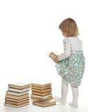 Una bambina che alza un grande libro Immagine Stock