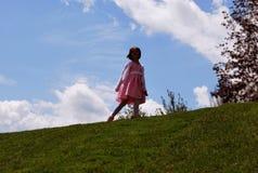 Una bambina che cammina sulla collina Fotografie Stock