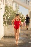 Una bambina che corre sotto sotto l'acqua corrente Immagini Stock Libere da Diritti