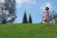 Una bambina che gioca sulla collina Immagine Stock