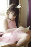 Una bambina che legge un libro Fotografie Stock