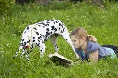 Una bambina che legge un libro all'aperto Fotografia Stock