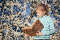 Una bambina che legge un libro su un albero del fiore Fotografia Stock Libera da Diritti