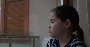 Una bambina che si siede dalla finestra nel giorno piovoso stock footage