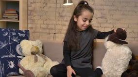Una bambina che si siede sullo strato e che gioca con una pecora dell'orsacchiotto, giocattoli molli, comodità domestica nei fps  video d archivio