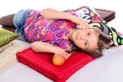 Una bambina che si trova sul suo telefono del letto Immagine Stock Libera da Diritti
