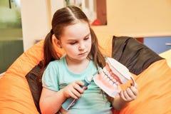 Una bambina in una clinica dentaria che tiene un manichino dentario immagine stock