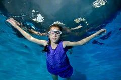 Una bambina con le trecce impegnate negli sport, nel underwater di nuotate nello stagno in un costume da bagno porpora e negli sg immagine stock
