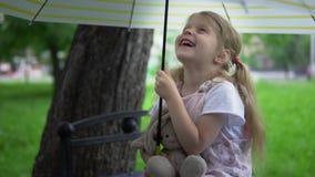 Una bambina con una lepre del giocattolo si siede su un banco sotto un ombrello stock footage