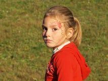 Una bambina con un trucco del fronte e uno sguardo pensieroso fotografie stock libere da diritti