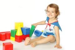 Una bambina costruisce una casa. Fotografia Stock