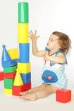 Una bambina costruisce una casa. Fotografie Stock