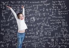 Una bambina davanti alla lavagna con le formule ed i calcoli fotografia stock libera da diritti