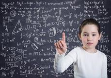 Una bambina davanti alla lavagna con le formule ed i calcoli fotografia stock