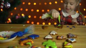 Una bambina decora il pan di zenzero accanto ad un albero di Natale nella sera video d archivio