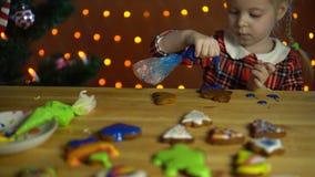 Una bambina decora il pan di zenzero accanto ad un albero di Natale nella sera archivi video
