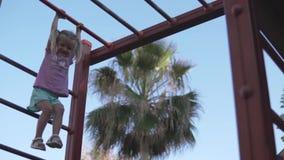Una bambina di sport ha scalato sulla cima delle scale nel campo da giuoco stock footage