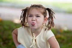 Una bambina divertente con gli occhi scuri con un taglio di capelli sotto forma di Immagine Stock Libera da Diritti