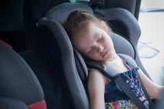 Una bambina dorme in una sede di automobile comoda per i bambini immagine stock libera da diritti