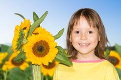 Una bambina e girasoli Fotografie Stock Libere da Diritti