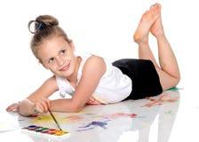 Una bambina estrae le pitture sul suo corpo fotografia stock libera da diritti
