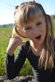 Una bambina gioca su un telefono immaginario Fotografie Stock Libere da Diritti