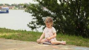 Una bambina piacevole disegna il gesso sulla traccia accanto alla passeggiata di lungomare video d archivio