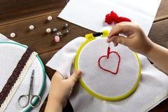 Una bambina ricama un cuore su una vista bianca del panno da sopra gli accessori per ricamo su fondo di legno fotografie stock