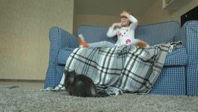 Una bambina salta su un sofà in una stanza, un gatto grigio si sederà dopo video d archivio