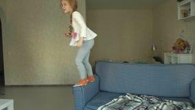 Una bambina salta su un sofà in una stanza, un gatto grigio si sederà dopo stock footage
