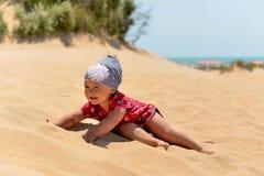 Una bambina in una sciarpa che gioca sulla spiaggia sabbiosa immagini stock libere da diritti