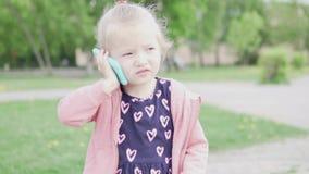 Una bambina si siede su una bicicletta e sui colloqui su un telefono del giocattolo stock footage