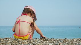 Una bambina sola raccoglie i bei ciottoli su una spiaggia del mare Si siede su un ciottolo, retrovisione stock footage