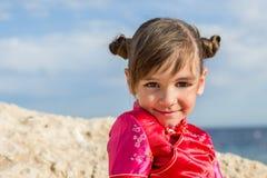 Una bambina sopra con i grandi occhi parte-osservati è messa e sorrisi spazzolati del japanesque su un fondo un mare della roccia Immagini Stock Libere da Diritti