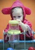 Una bambina sperimenta con acqua al ` s dei bambini di scoperta Fotografia Stock