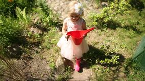 Una bambina sta camminando nel giardino con un annaffiatoio rosso archivi video
