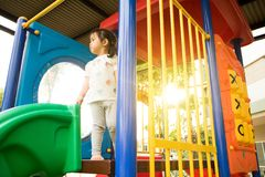 Una bambina sta giocando in campo da giuoco Fotografia Stock