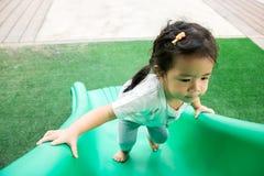 Una bambina sta giocando in campo da giuoco Immagini Stock